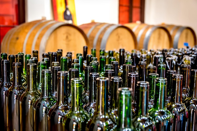 Rows of green wine bottles in front of wine barrels at Bahama Barrels winery in Nassau, Bahamas.