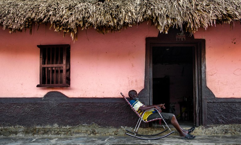 KYXN3B An old Colombian man sits in a rocking chair in front of his house in San Basilio de Palenque, a village in the Caribbean region of Colombia.