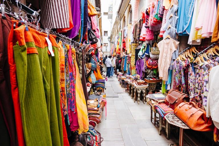 Colourful clothes and leather souvenirs in the touristic Alcaiceria souvenirs market. Granada, Andalusia, Spain