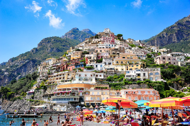 Colourful beach scene on the Spiaggia Grande (main beach) in Positano, Italy. Vacationers relaxing under umbrellas with the town towering above