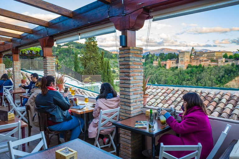 Granada, Spain: Tourists at El Balcon de San Nicolas cafe and restaurant in the Albaicin district old town, enjoy a panoramic view of the Unesco liste