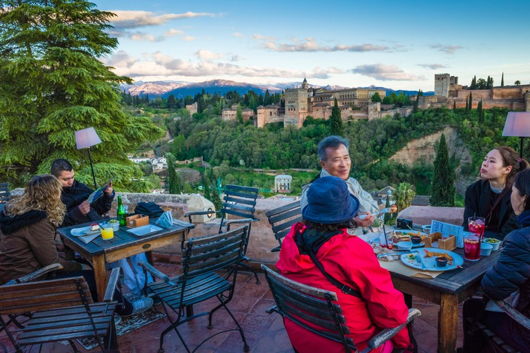 Granada, Andalusia, Spain - April 29th, 2018 : Tourists at Huerto de Juan Ranas cafe and restaurant in the Albaicin district old town, enjoy a panoram