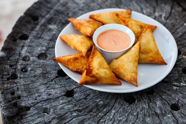 Delicious fresh homemade crispy samosas with sauce