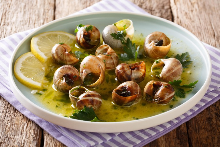 Delicatessen food: edible snails, escargot cooked with butter, parsley, lemon and garlic close-up on a plate on the table. horizontal