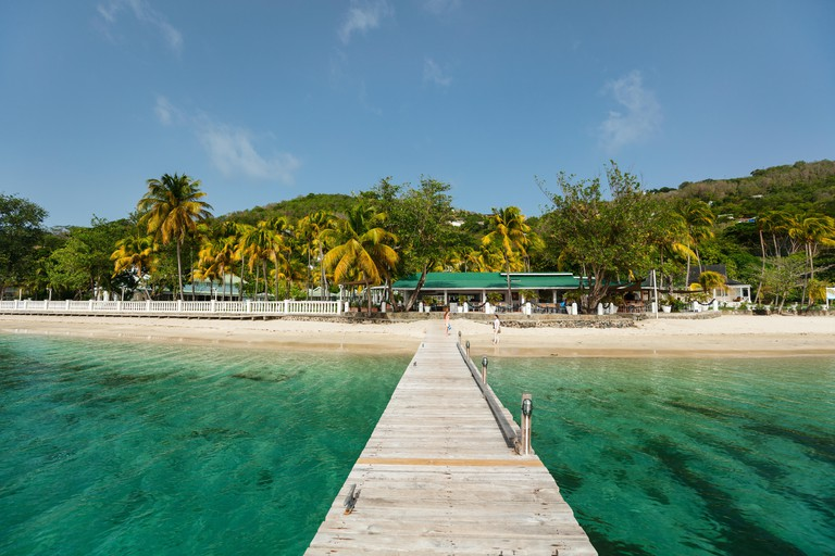 PGGD42 Tranquil tropical beach with white sand, palm trees and turquoise Caribbean sea water on Bequia island in St Vincent and the Grenadines