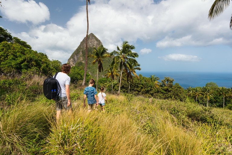 Family of father and kids hiking on summer day at tropical island of St Lucia in Caribbean with amazing views to iconic Pitons mountain