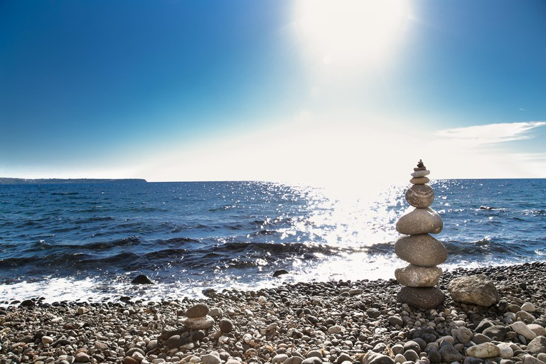 PNK2TT Stone pebbles stacked, ancient ritual for good fortune and prosperity at Black Katharos Beach on Santorini island, Greece.