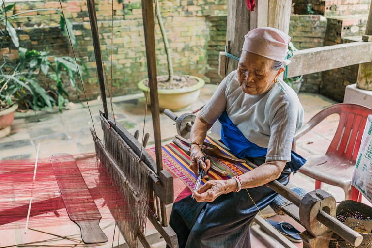 Lac Village, Mai Chau Valley, Vietnam - October 18, 2016. Local woman diligently working at a loom, weaving colourful brocade fabric.