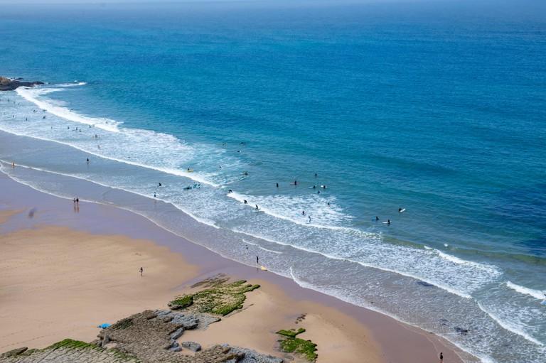 Surfing in Foz do Lizandro beach, Ericeira, Portugal