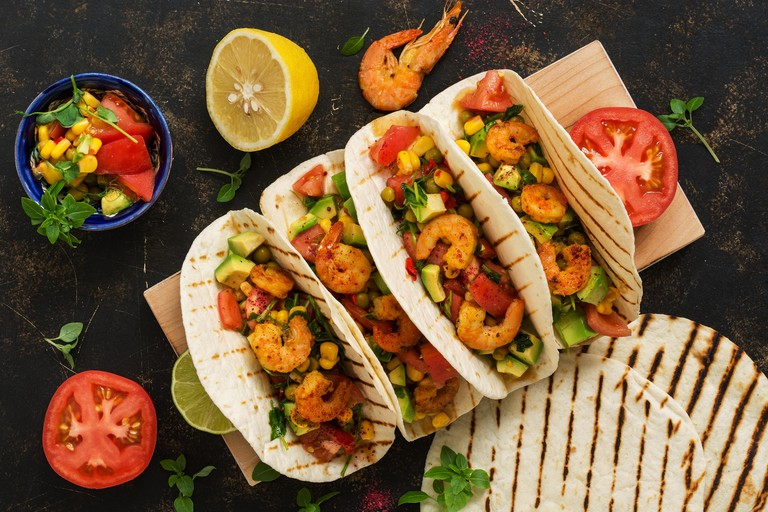 Mexican food. Homemade tacos with shrimp, avocado and salsa sauce on a dark rustic background.