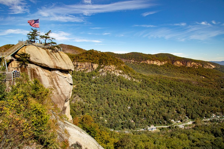 Chimney Rock with American flag flying at Chimney Rock State Park in the foothills of Hickory Nut Gorge North Carolina