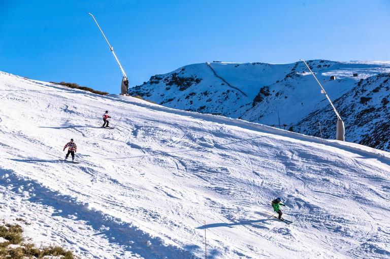 Skiers on mountainside of Sierra Nevada mountain in Spain region