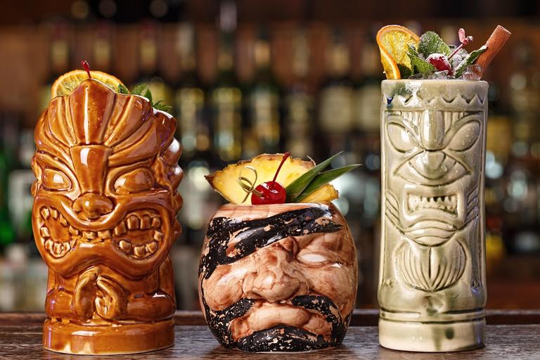 Set of three tropical cocktails in tiki glasses - pina colada, rum runner and rio punch. Menu image