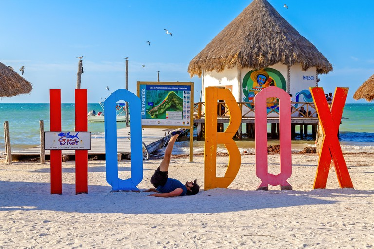 T485W7 Tourist with the Holbox sign on the beach, Isla Holbox, Mexico