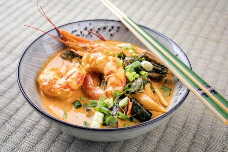 Traditional Thai kaeng phet red curry with king prawns and vegetable as top view in a bowl on place mat. Image shot 10/2018. Exact date unknown.