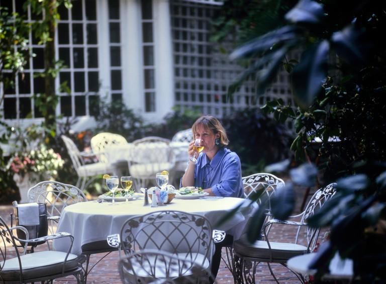 Woman having lunch in a restaurant garden courtyard. The Veranda, Fort Myers. Florida. USA
