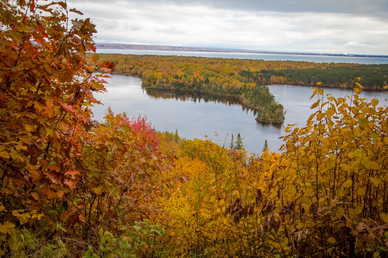 Michigan Autumn Scenic Panorama. Vibrant autumn color in the northern Michigan forest with the vast blue waters of Lake Superior in the background.