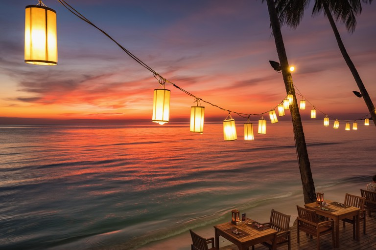 Romantic sunset on the shore of a tropical island, Koh Chang, Thailand. Outdoor cafe on the beach.