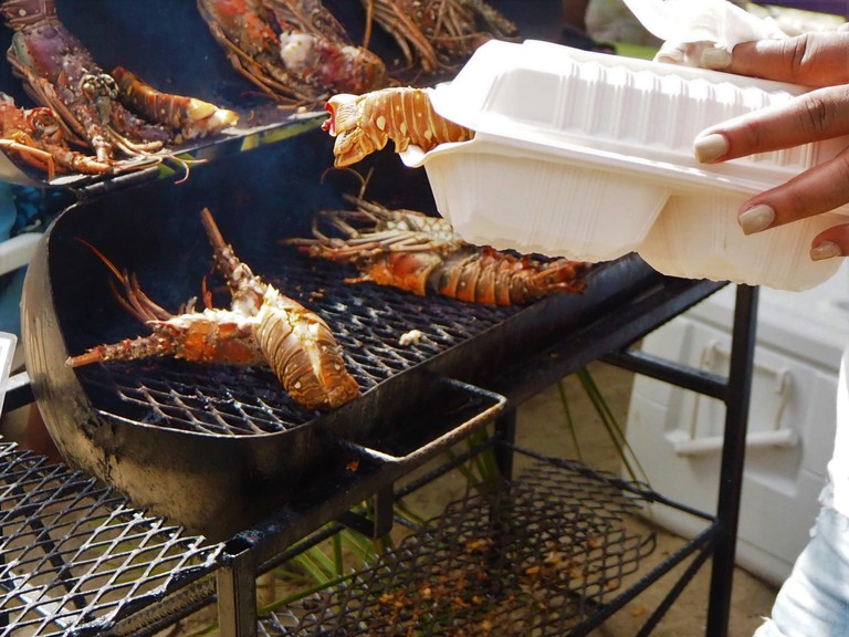 BBQ Lobster Placencia Lobster Festival, Belize, Caribbean. Bar Be Que for take away in plastic container. barbecue
