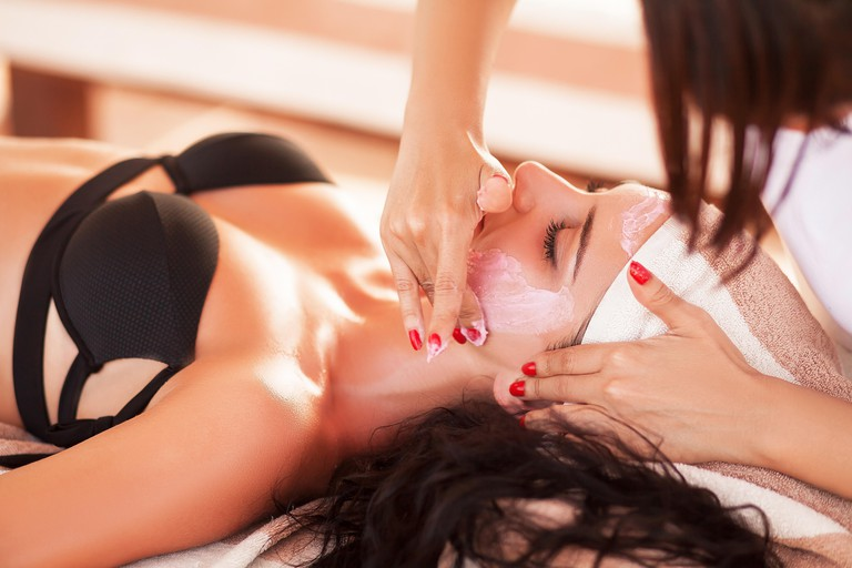 W8N4GT Spa and massage. Pretty woman in spa salon in sunny beach get face and back massage