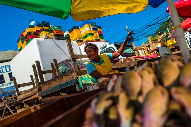 An Afro-Colombian woman sells fresh fish in the market of Bazurto in Cartagena, Colombia.