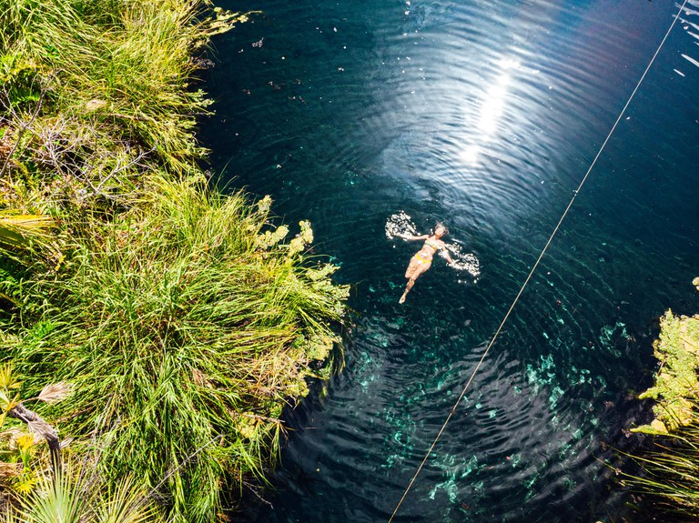 Woman swimming in clean water of Cenote Crystal