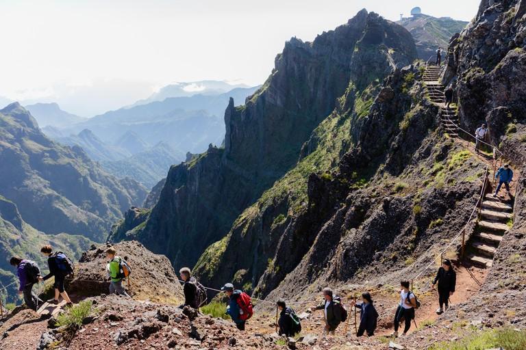 "PICO DO AREEIRO, MADEIRA - SEPTEMBER 2019: Group of tourists hiking in the mountains of Madeira from ""Pico do Areeiro"" to ""Pico Ruivo"" on a cloudy sum"