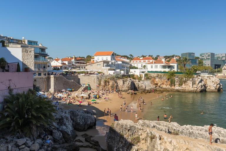 Crowded Praia da Rainha (Queens's Beach) in downtown Cascais, Portugal, on a sunny day.