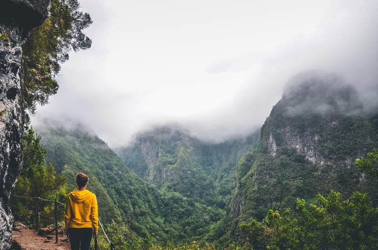 Young woman in yellow sweatshirt on a viewpoint in Levada Caldeirao Verde, Madeira, Portugal. Green scenic mountains in fog, misty landscape. Female traveler. Instagram, hipster filter.