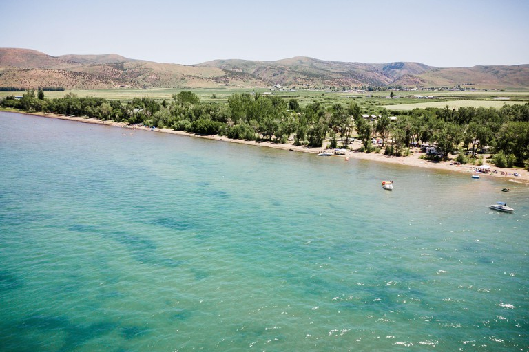Drone shot of famous blue water of Bear Lake Utah, boats and people in water