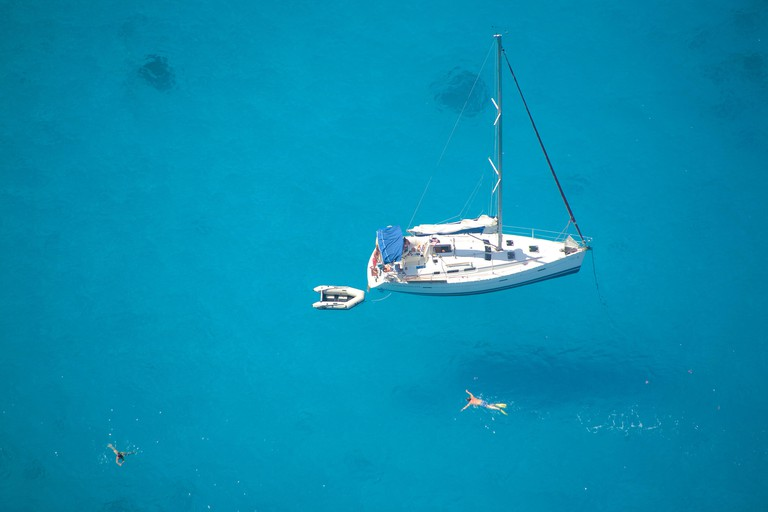 Swimming people in Shipwreck Bay, one of the most beautiful beaches in Greece, Zakynthos island, Greece