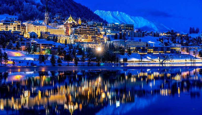 View of beautiful night lights of St. Moritz in Switzerland at night in winter, with reflection from the lake and snow mountains in backgrouind
