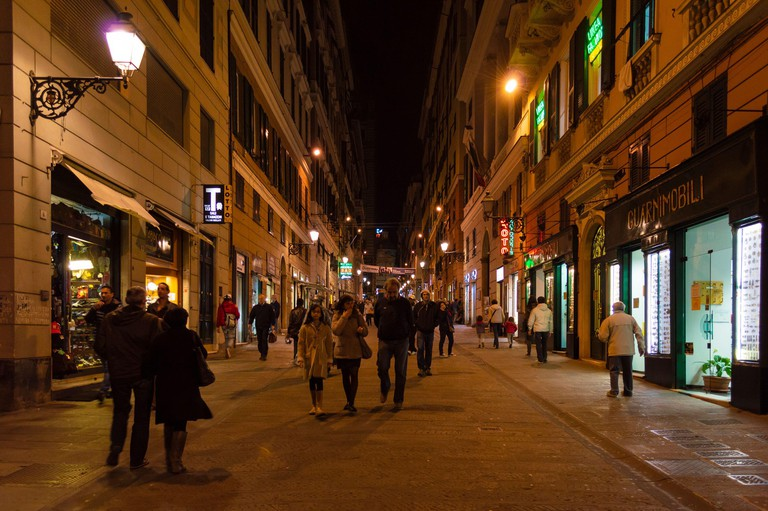 An alley in Genoa with a lot of pedestrians. Night life in Genoa.