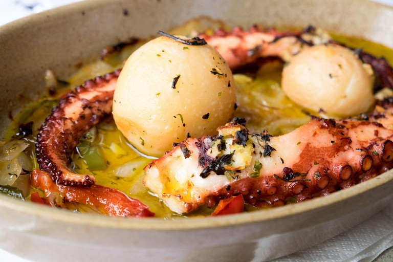 Traditional portuguese dish popular on Madeira island - polvo a lagareiro, octopus with baked potatoes and olive oil.