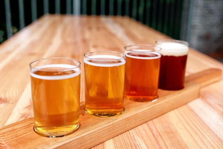 Beer tasting. Diferent beer in 100 mililiter glases over wooden table.