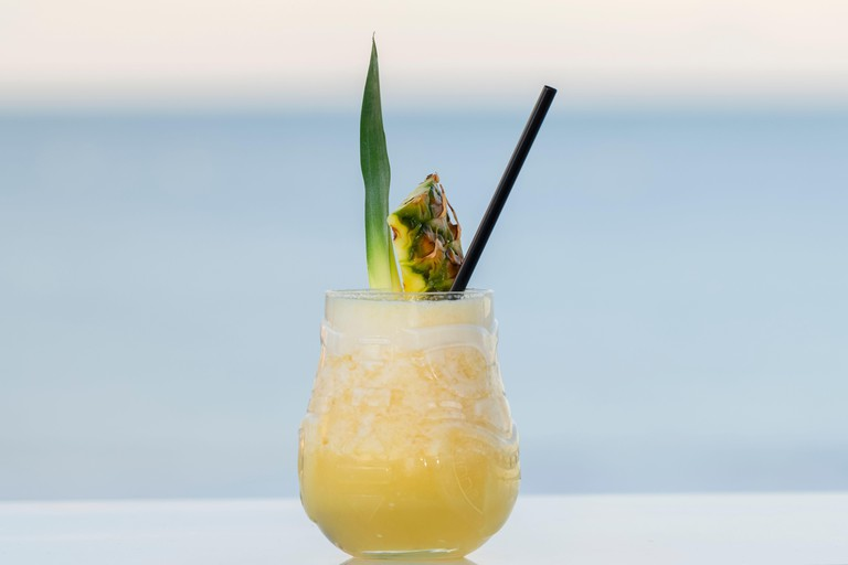 Delicious looking pina colada cocktail with a straw, a pineapple slice and a leaf on an out of focus background. Selective focus and close up.