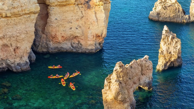 Aerial view of rocky coast in Ponta da Piedade in Lagos, with kayak group in clear ocean water. Portugal. Lagos.
