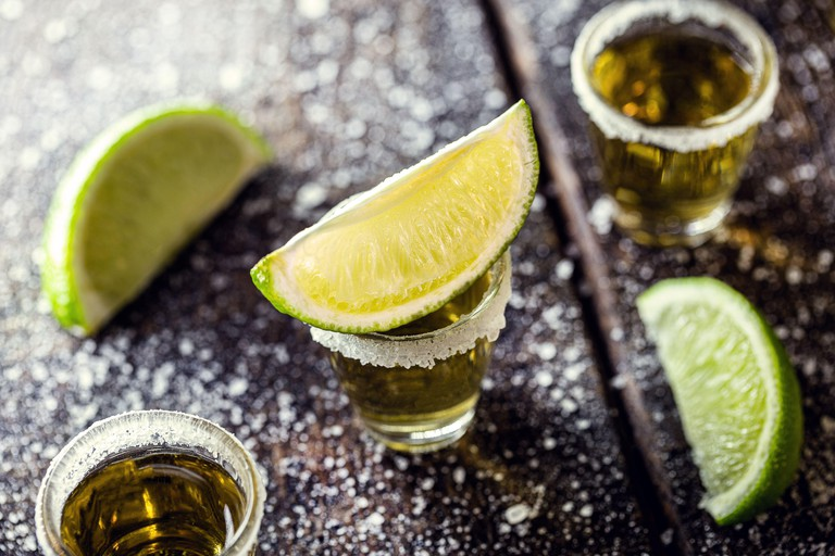 glass of tequila, a drink of Mexican culture, made of distilled alcohol, lemon, salt and blue agave. International tequila day.