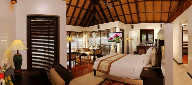 A bed, desk and sitting area in a hotel room with a wooden beamed ceiling at Carnoustie Ayurveda Beach Resort & Spa