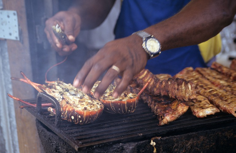Lobster being cooked on a Barbecue with cooks arms and smoke in Anguilla Caribbean
