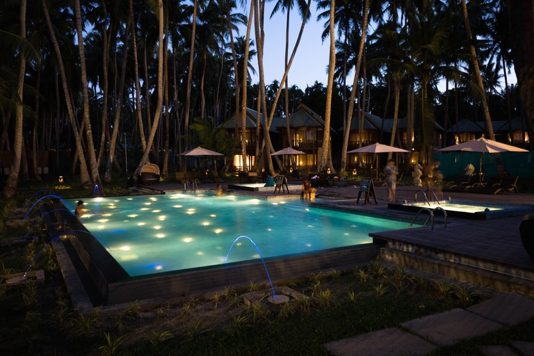 The outdoor pool, surrounded by tall trees and the chalets of Seashell Havelock
