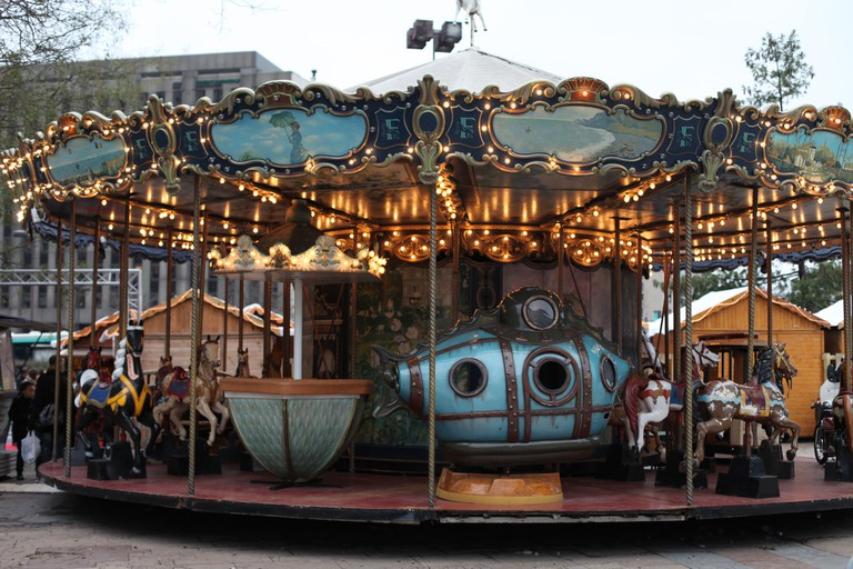 It's a photo of an old style carousel during winter in front of Montparnasse tower in Paris, France. For Christmas Time
