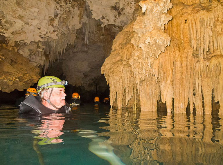 CTGMX8 Swimming man looks at fantastic rock formations at Rio Secreto, an underground cave that people can visit in Mexico