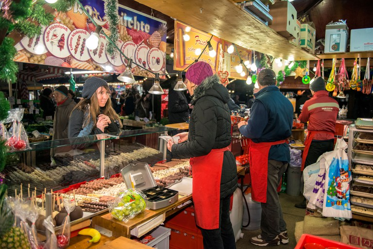 Christmas market vendor selling chocolate covered fruit on a stick, Wurzburg, Germany