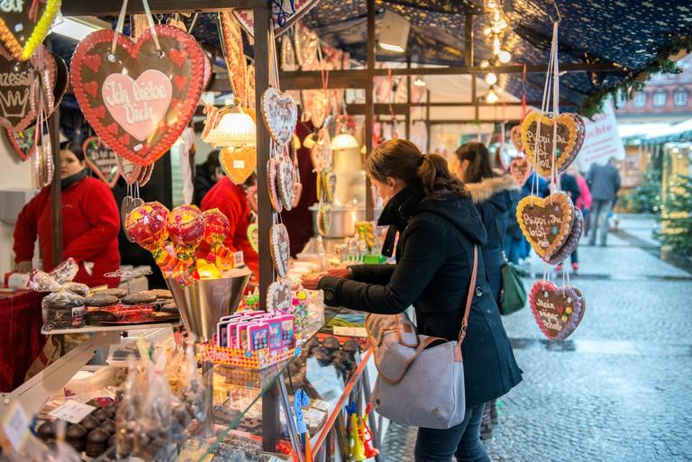 Woman buying gingerbread at Christmas Market, Bamberg, Germany