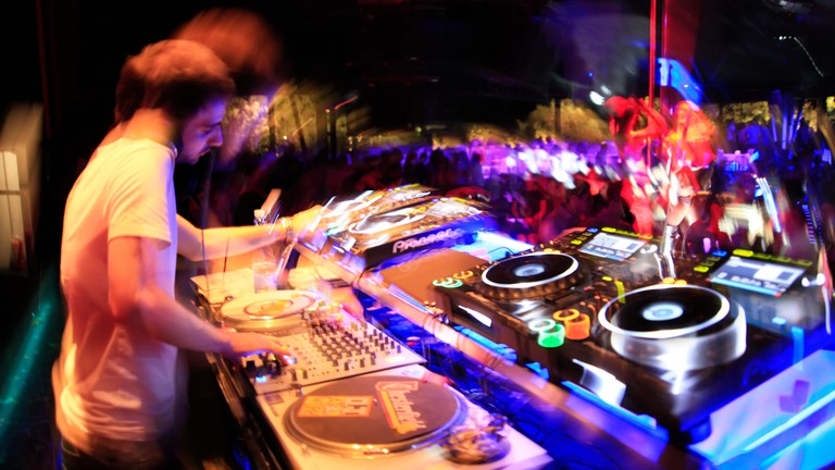 Image full of motion blur of a DJ on the decks / sound audio mixing decks devices and dancing clubbers. Athens nightclub, Greece.