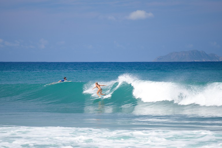 Female surfer catching a wave at Dome's Beach. Rincon, Puerto Rico. USA territory. Caribbean Island.