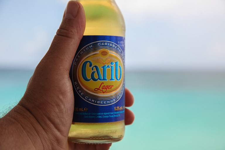 Ice cold Carib beer in mans hand
