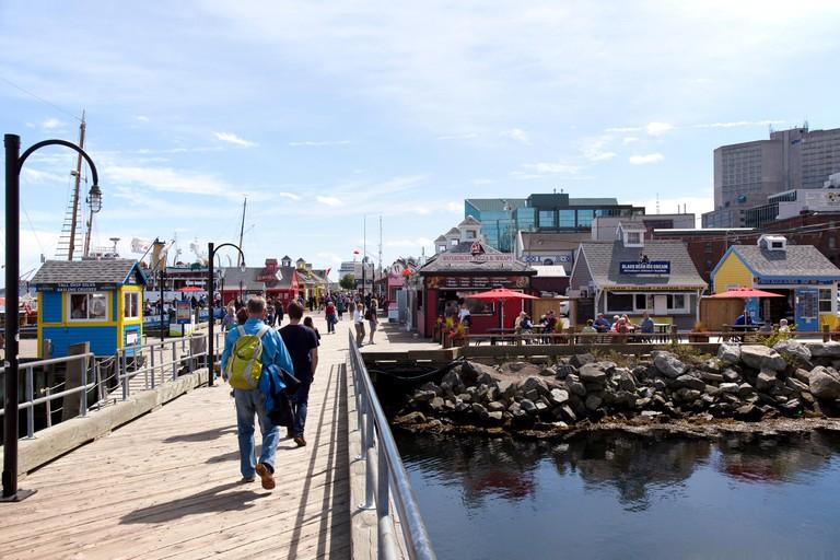 Tourists walking along the Waterfront boardwalk in Halifax , Nova Scotia