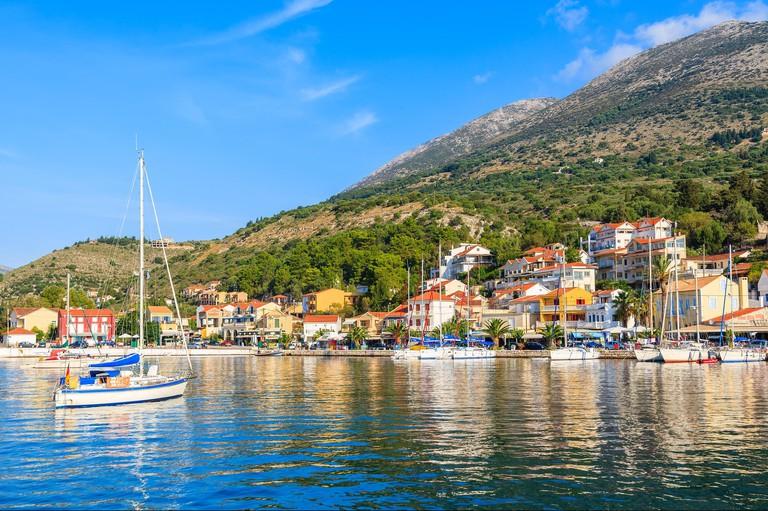 Yacht boat on sea and view of Agia Efimia village on Kefalonia Island, Greece
